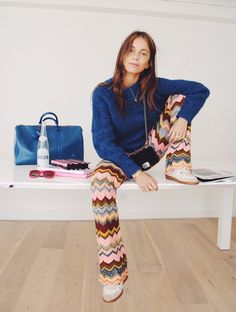 Lizzy van der Ligt wears a fuzzy blue sweater, patterned flare pants, sneakers, and a mini Chanel bag