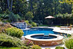 comment aménager son jardin avec une piscine extérieure et une cascade en pierre naturelle