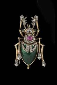 20th century Scarab Brooch: 14k rose gold, diamonds, emerald, ruby, and dark green enamel.