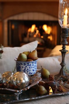 Beautifully done arrangement.  I love all the layers, silver on silver, the blue bowl, pears, tall candle holder, fire in the background...........