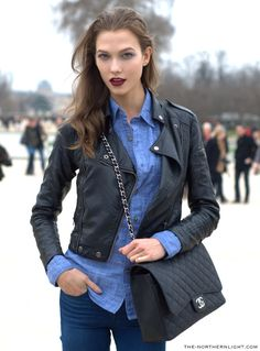 469f9bec704 Karlie Kloss in A black leather jacket over a chambray collared shirt and  paired with blue Jean pants. Dark plum lips and black