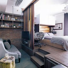 It started with a red brick wall. And Kurt Reyes built his living area around it, with shelves of plumbing pipes and wooden planks. Then, a gray tufted couch, a tree stump as side table, and an LCD TV on the wall opposite. Condo Interior Design, Condo Design, Studio Design, Small Condo Living, Living Area, Living Room, Studio Type Condo, Tiny Studio, Small Condo Decorating