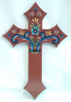 "rosemaling hand painted cross  dark red background  blue scrolls, gold. white, blue flowers  finished with polyurethane  non warping wood base  excellent addition to a cross wall  18"" high, approx. 3/4"" thick  one of a kind - original  signed  ready to hang in an interior setting 