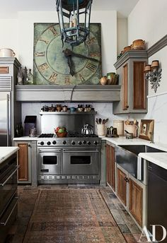 The room's cabinetry incorporates reclaimed English wainscoting; the clock is a French antique, the range is by Viking, and the stainless-steel sink is by Franke.
