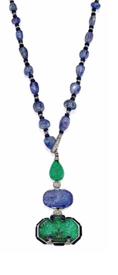 THE BARON DE ROTHSCHILD NECKLACE - Elegant & Rare Platinum, Emerald, Sapphire, Lapis Lazuli & Diamond Pendant-Necklace, Designed by Charles Jacqueau for Cartier, Paris - In the style of Mughal Empire art, the necklace comb ining elements of Indian & Persian decorative traditions, the pendant suspending a hexagon-shaped emerald, an oval-shaped sapphire & a pear-shaped emerals, all carved with Mughal floral motifs, completed by a necklace composed of 41 sapphire beads...