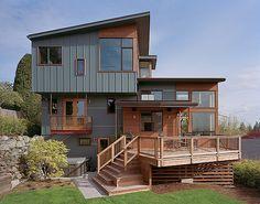 Vertical siding with horizontal cedar and black windows.