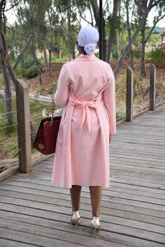 Burgundy metal strap bodycon dress with pink shawl collar coat with ankara tote handbag and gold strap shoes