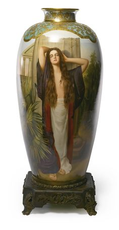 A LARGE VIENNA-STYLE IRIDESCENT GREEN-GROUND VASE OF 'BIEN ÊTRE' LATE 19TH/EARLY 20TH CENTURY the bulbous body painted with a full-length portrait of a beauty wearing a kimono beneath the neck and shoulder decorated in raised gilding with stylized foliage in Art Nouveau style mounted on a gilt-bronze square plinth. height 27 in. 68.5 cm