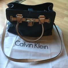 Calvin Klein Leather Shopper Tote Very gently used Calvin Klein navy blue pebble leather shopper tote.  Center zip, 2 interior slip compartments and 1 zip, 1 exterior card slot, 2 pockets on exterior ends.  Chain detail on straps, snap closure on interior.  No damage, very little strap wear and only on the crossbody strap.  Slight scratching in metal beneath faux-lock feature.  Beautiful and large bag, it easily held my laptop, iPad, files, and wallet.  Includes original dust bag and card…