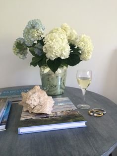 Tabletop Decorator Tip!  Create Easy Elegant Tabletops with books. Depending upon the size of the table create small stacks of books. Add a vase of flowers, and then place an accessory on one of the book stacks. A large seashell spins this design towards coastal, or substitute a small wooden box, an animal figurine or a small photo in a decorative frame for your own personal style message. Sponsored by HomeGoods.