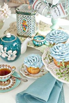 tea table in light blue, frsoted cupcakes and a vintage tea cup
