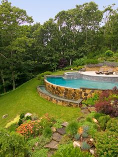 An arc-shaped pool with a spa is built into the hillside, where cascading water gently rolls over the Misty Rose flagstone veneered pool wall, producing a calming effect. The infinity edge is designed to spill into a raised trough that doubles as a sitting area and water sculpture.
