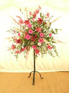A large scale deep pink and red pedestal flower arrangement . Helen Allen. Verdila
