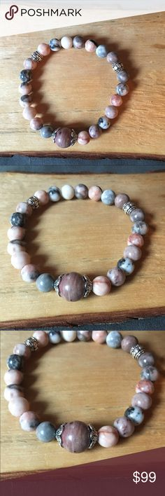 Pink and grey jasper bracelet Gorgeous pink and grey jasper bracelet with silver accents and a center rhodonite stone.  Jasper in known to draw positive energy.  Jasper is also known to be great for healing and cleansing.  While stones and crystals have been used since the beginning of time, it is not a substitute for medical care. Please seek professional help when needed.  Each piece is handmade with lots of love and positive energy. Jewelry Bracelets