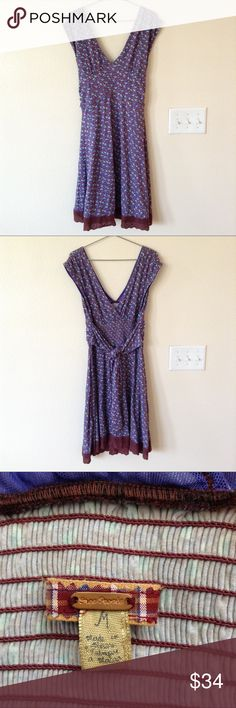 Free People Sleeveless Purple Print Dress This dress features a fun purple and light teal pattern with a dainty brown lace across the bottom. The front and back necklines make a V-shape. There is a nice long tie in the back to adjust the waist. Free People Dresses