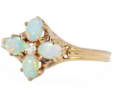 Vintage opal ring, forming a flower motif with 4 white oval cabochon opals in a cluster around an old European cut diamond, est. .02 carats, 10k yellow gold, circa 1920