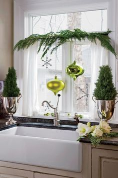 Bring the holiday cheer to your kitchen by adding rosemary plants, evergreen branches, and bold ornaments as decorative details.