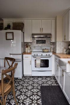 Retro kitchen appliances. White kitchen cabinets. Beveled subway tile. Patterned floor tile.