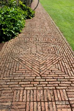 Photo showing an old block paved pathway, with weathered / aged red bricks that are full of character. The bricks in this path have been laid out in a mixture of different patterns, including stack.