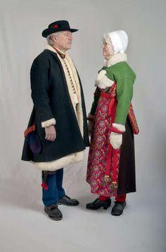 Kyrkdräkt på vintern. Kvinnan är gift och visar det genom att bära hatt. Knytningshatten, en hatt med spets, används till första och andra rangens kyrkosöndagar året runt. Mansdräktens varianter är inte lika många som kvinnodräktens. Boda, Sweden.