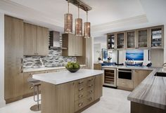 The designer's architectural grounding allowed her to devise cached ducting, elevated ceilings and stepped molding for this kitchen. Against its white, Hamlin Woodworks' sycamore cabinetry appears as an elegant foil for the sparkle of pulls and Global Views' dazzling pendants.