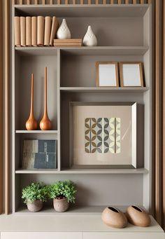 Decoração de apartamento pequeno e charmoso com ambientes integrados com ripas de madeira. Nichos com quadros, plantas e adornos.