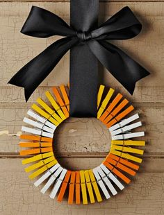 Cute clothespin wreath in candy corn colors! Details: http://www.midwestliving.com/homes/seasonal-decorating/halloween-decorating-ideas/?page=1