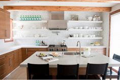 Kitchen design tip for open shelving: Keep the shelf design simple so that it doesn't compete with the items set on it, but make sure the design coordinates with the style of your kitchen. Use our Free-Hanging Shelf Bracket to create a floating shelf with hidden brackets for a clean look. Photo by Alice Lane Home via Houzz.