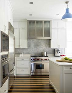 The mosaic tile, stainless steel accent cabinets,m striped hardwood floor.