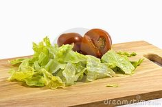 A close up of fresh tomatoes and lettuce on a wooden chopping board