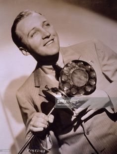 1932: Sepia-toned image American singer and actor Bing Crosby (1903-1977) holding an old-fashioned microphone, in a promotional portrait for the film, 'The Big Broadcast.'