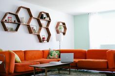 cushy orange sofa and honey comb wall decor! wonderfully homey.