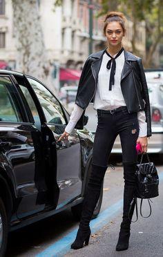 Modelo tira foto para street style parada abrindo a porta do carro, usando calça jeans preta distroyed, over the knee boots, mochila chanel, camisa branca, skinny scarf preto, jaqueta de couro preta e batom vermelho