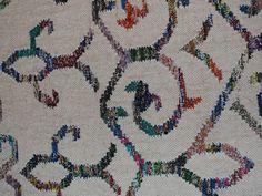 Tettvevd teppe med multifargete ornamenter i hvit bakgrunn