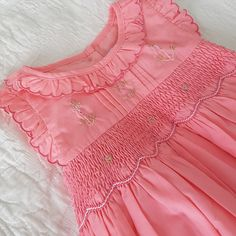 A must have for summer.... A gorgeous coral pink hand smocked dress.