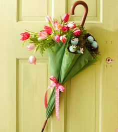 Beautiful Easter Door Decoration:.      Pink tulips, along w/ greenery & dyed eggshells filled w/ daffodils, tuck neatly into umbrella for unique Easter door decor. Tie a pretty pink ribbon halfway up closed umbrella to create a makeshift vase for arrangement. Create pockets 'tween front ribs, tuck in tissue to support a crafts-store nest, blown-out Easter eggs, flowers, & greenery, like ferns & moss. To finish, wire arrangement to a front-door hook to hang. Keep blooms fresh, in water vials.