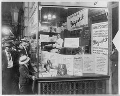 """Shoppers looking at window display of Brown's Drug Store, advertising """"Digestit,"""" a stomach relief patent medicine; product is being endorsed by a pianist, """"Mr. Thomas,"""" who has been playing in the store window non-stop for 60 hours and 45 minutes.  April 9, 1915"""