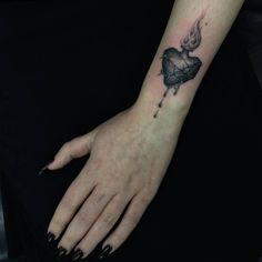 Pequeño tatuaje de un corazón en llamas situado en la muñeca...
