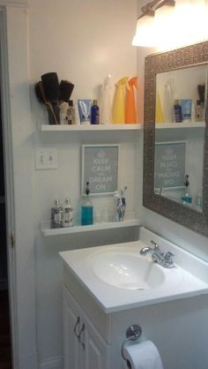 Small bathroom storage idea - By-the-sink shelving using IKEA RIBBA picture ledges.