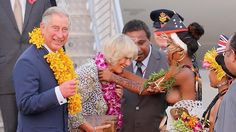 A topless dancer places garlands on Prince Charles, Prince of Wales and Camilla, Duchess of Cornwall as they arrive into Jackson's International Airport in Port Moresby. Source: Getty Images