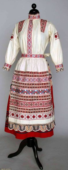 "Augusta Auctions, April 17, 2013 - NYC, Lot 118: Woman's Regional Dress, Slovakia, 1920s 3-piece cotton: white blouse & apron embroidered in red & blue cross stitch w/ white, purple & pink bobbin lace trims, red skirt w/ embroidered navy bands, B 33"", W 25"", Skirt L 30"", (underarm stains) very good. BM"