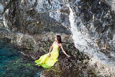 Beautiful brunette girl in yellow dress sits on a rock near mountain lake