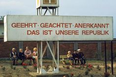 "ThŸringia. Weimar. 1974. A political billboard near a railway station reads: ""Honored, Respected, Recognized - that's our Republic."""