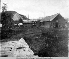 "View of Tonsina Roadhouse, a group of log buildings in a clearing, a sign hanging over the smaller log building reads, in part: ""Fred and Jake Tonsina Road House"" and a horse stands next to the building. A canvas tent is visible in the background and a dog stands near building at right. [Frederick John, Archives and Special Collections, Consortium Library, University of Alaska Anchorage UAA-hmc-0379-series2-v2-63a]"