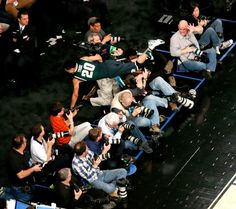 Travis Trice (20) dives over photographers after trying to keep a ball in bounds during second half in a regional semifinal against Virginia at the NCAA men's college basketball tournament, Friday, March 28, 2014, in New York. (AP Photo/Julio Cortez)