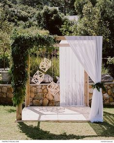 An installation of lush greenery and geometric ornaments decorated the arch at this garden wedding ceremony.