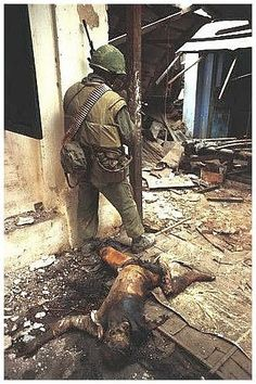 An American soldier is alert. At his feet is a dead Vietcong.