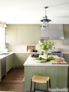 "Madeline Stuart concocted the ""modern Provincial"" kitchen in a California house with minimalist grooved cabinetry, in a soft custom green, and limestone countertops. ""The kitchen needed to be somewhat masculine, but still warm and inviting,"" she says.   - HouseBeautiful.com"
