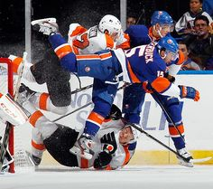 Cal Clutterbuck of the New York Islanders takes a couple of Philadelphia Flyers down with him as he crashes the crease.