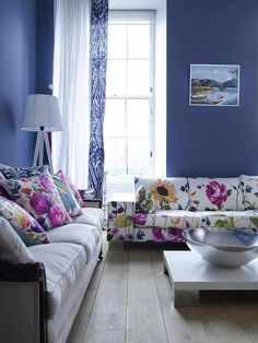 Living room color schemes: Color doesn't always have to be sunny and bright.  This deep-indigo living room provides the perfect backdrop to feminine furnishings doused in look-at-me floral prints.  Designer Fiona Douglas avoided an overabundance of patterns by creatively mixing ikat and floral designs [OMGenius!] with white accents, creating the perfect color balance.